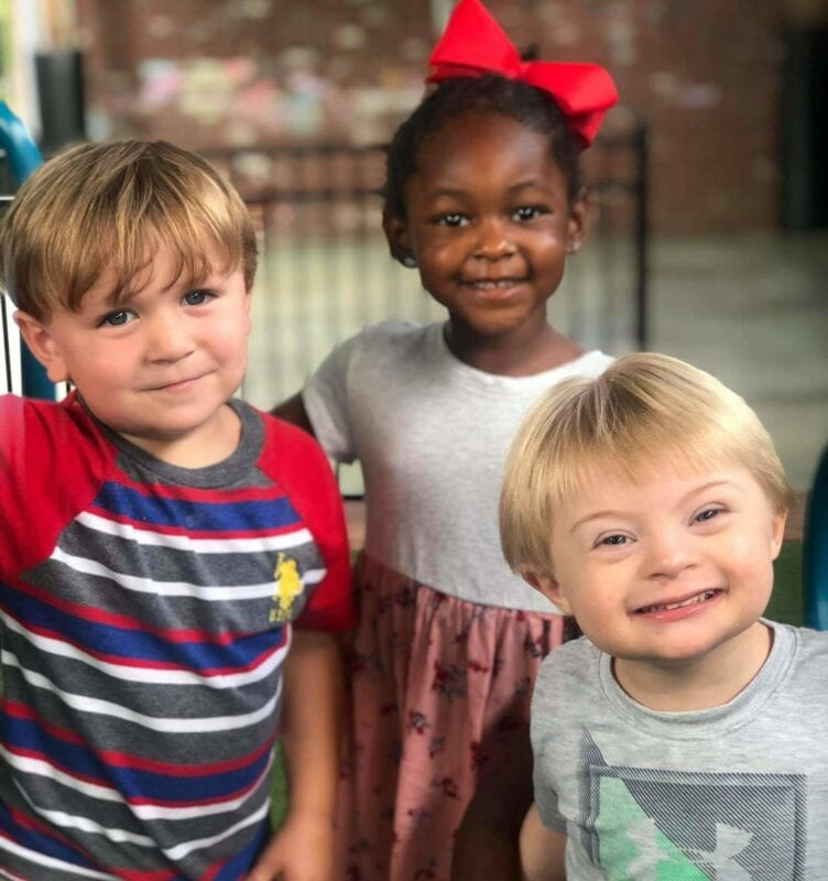 Three smiling children outside